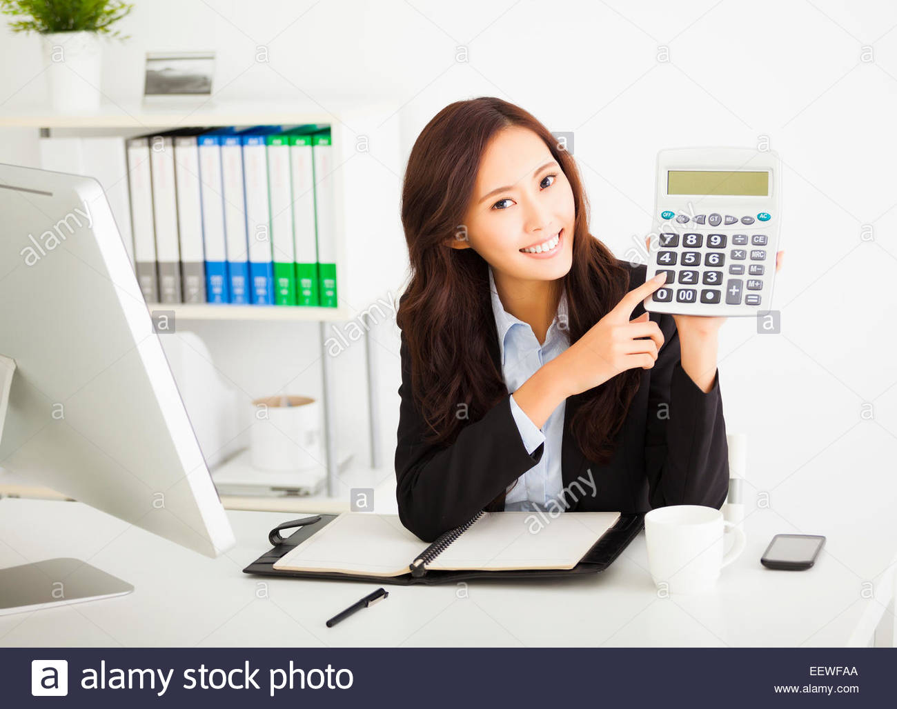 smart-business-woman-showing-the-calculator-in-office-EEWFAA